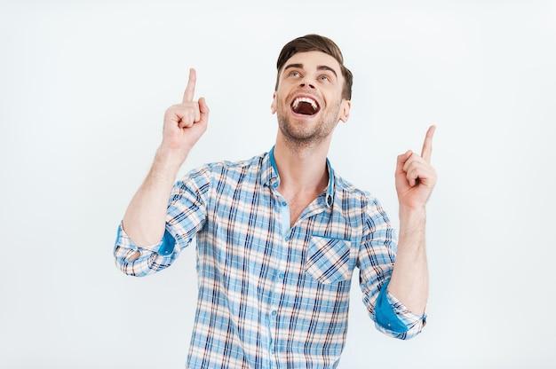 Fröhlicher präsentator ihrer anzeige. glücklicher junger mann im hemd, der nach oben zeigt
