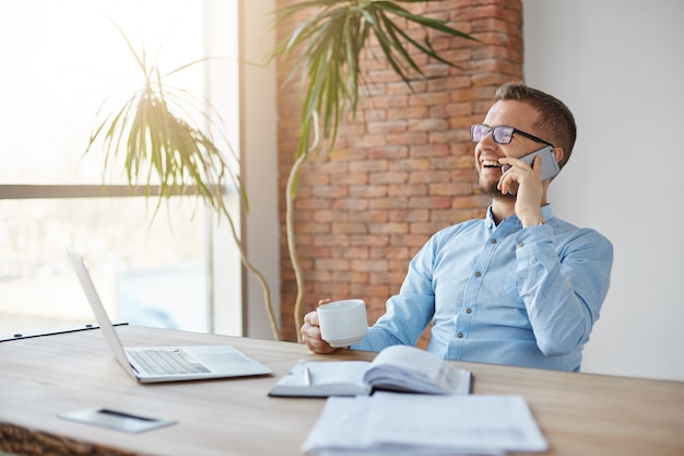 Fröhlicher professioneller erwachsener kaukasischer finanzmanager in den gläsern und im blauen hemd, die im firmenbüro sitzen