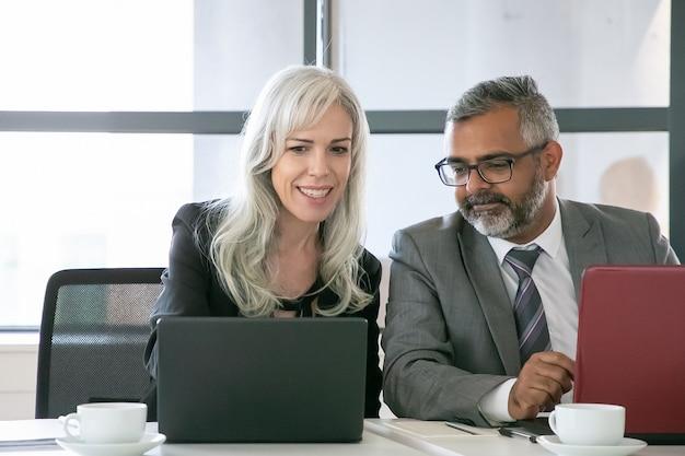 Fröhlicher projektmanager, der dem kollegen im büro die präsentation auf dem laptop zeigt. mittlere einstellung, vorderansicht. teamwork und kommunikationskonzept