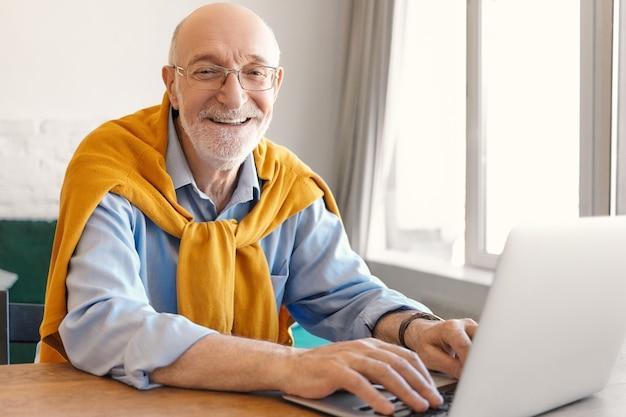 Fröhlicher reifer bärtiger kahlköpfiger männlicher unternehmer, der brille und pullover über blauem formellem hemd trägt, das glücklich lächelt, während er auf tragbarem computer tastet und videospiele während der mittagspause spielt