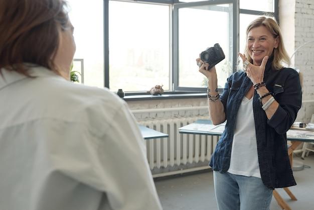 Fröhlicher reifer fotograf mit kamera, die modell bittet, im fotostudio zu lächeln
