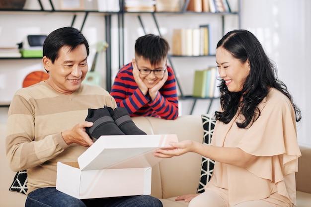 Fröhlicher reifer mann, der geschenk von seiner familie öffnet und neue schuhe herausnimmt, die er so sehr wollte