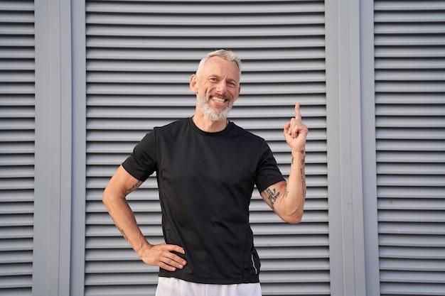 Fröhlicher reifer mann, der in die kamera lächelt, die hand hebt und den zeigefinger beim posieren nach oben zeigt