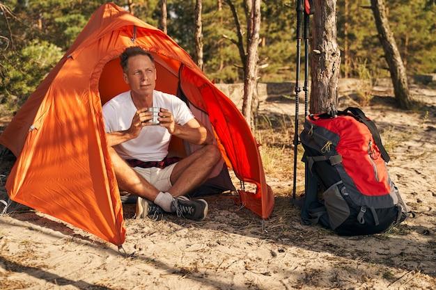 Fröhlicher reifer mann entspannt sich nach dem nordic walking im sonnigen wald mit einer tasse heißem getränk