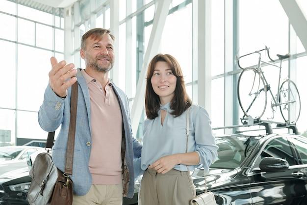 Fröhlicher reifer mann in eleganter freizeitkleidung, der seiner jungen lächelnden frau eine vielzahl von luxuriösen autos zeigt, während er ein großes autozentrum besucht, um ein fahrzeug zu kaufen