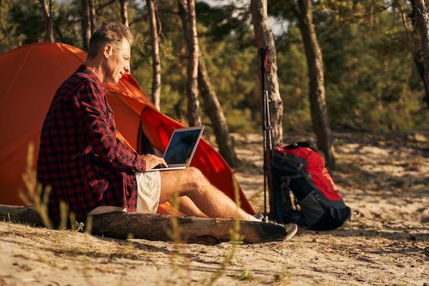 Fröhlicher reifer mann sitzt in der nähe des zeltes in der natur und tippt nach dem nordic walking auf dem laptop