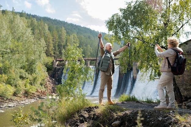 Fröhlicher reifer rucksacktourist, der seine hände mit trekkingstöcken hebt, während seine frau ihn während der reise auf smartphone-kamera fotografiert