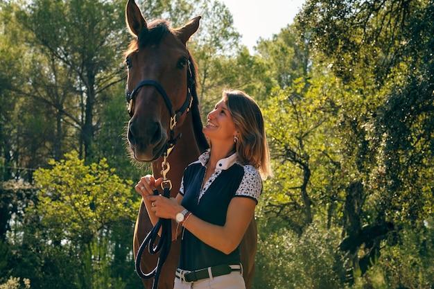 Fröhlicher reiter mit pferd im sommerwald