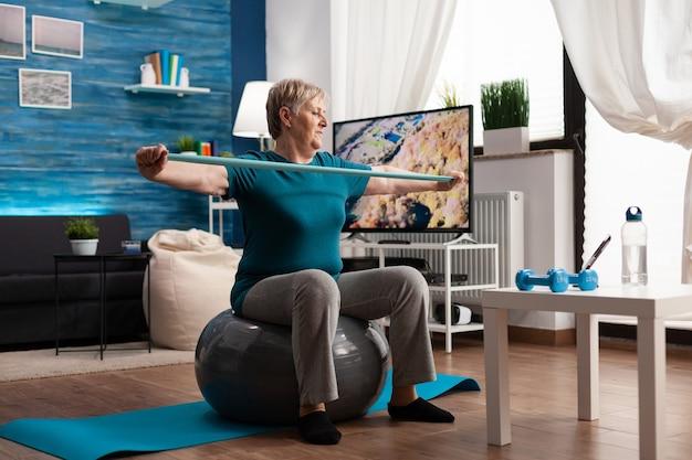 Fröhlicher rentner im ruhestand, der armmuskeln mit gummiband beim aerobic-training arbeitet. rentner, der auf einem schweizer ball im wohnzimmer sitzt und am widerstand im körpergesundheitswesen arbeitet und ein fitnessstudio-video anschaut