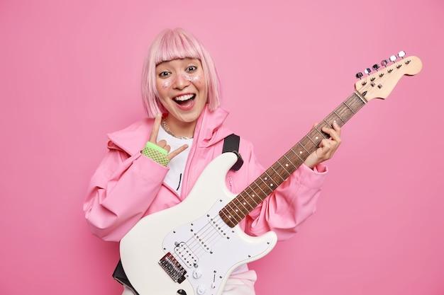 Fröhlicher rockstar macht horn-heavy-metal-schild als mitglied einer beliebten band oder berühmter solokünstler posiert mit akustischer e-gitarre hat trendiges rosa haar trägt modische kleidungsposen im innenbereich