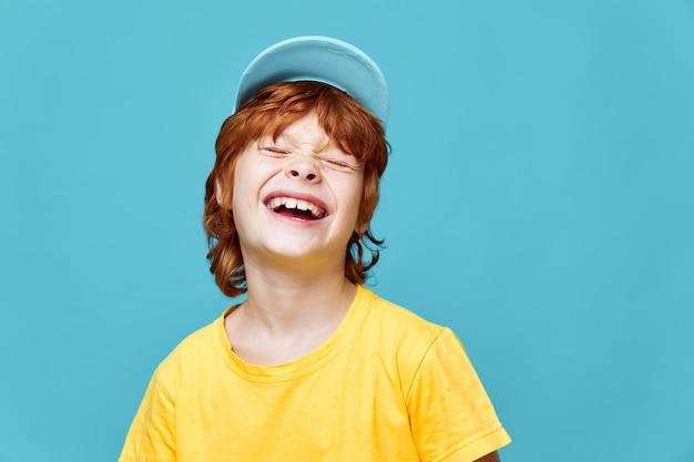 Fröhlicher rothaariger junge, der lachend seine augen schließt blaue gelbe kappe gelbes t-shirt beschnittene ansicht isolierten hintergrund