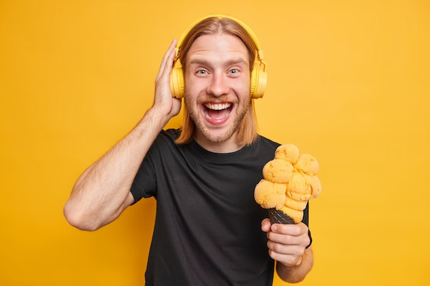 Fröhlicher rothaariger mann lächelt positiv, trägt stereo-kopfhörer, hört musik, isst köstliches eis, gekleidet in schwarzem t-shirt, isoliert über leuchtend gelber wand. sommerlebensstil