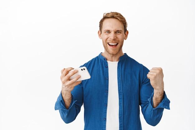 Fröhlicher rotschopf sagt ja, ballt die fäuste als gewinn auf dem handy, triumphiert, erreicht das erfolgsziel auf dem smartphone-app-videospiel und steht gegen die weiße wand