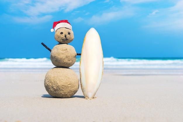 Fröhlicher sandmann aus weißem sand am sauberen strand einer exotischen insel auf dem hintergrund des blauen meeres und des bewölkten himmels. sandsurfer. kreative idee des surfens. das konzept des wassersports