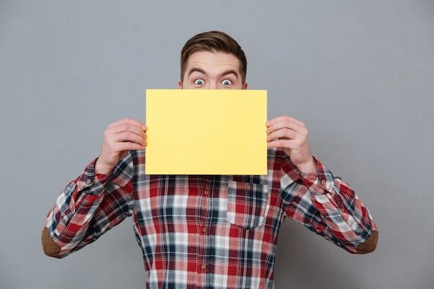 Fröhlicher schockierter junger bärtiger mann, der leeres papier hält