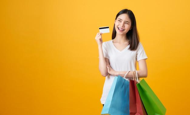 Fröhlicher schöner asiatischer teenager, der mehrfarbige einkaufstaschen und kreditkarte auf hellgelb hält