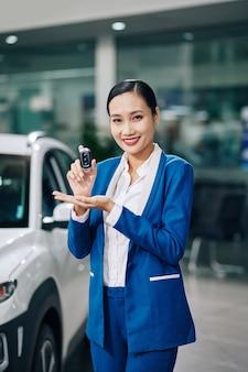 Fröhlicher schöner autohausarbeiter, der elektronische schlüssel des neuen autos zeigt