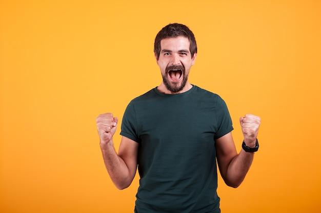 Fröhlicher schreiender aufgeregter mann mit offenem mund von emotionen auf orangegelbem hintergrund. portrait von ausdruck und glück