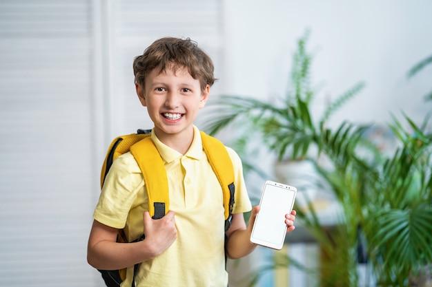 Fröhlicher schüler mit rucksack zeigt weißen handybildschirm. e-learning.