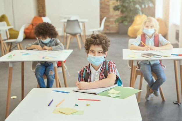 Fröhlicher schuljunge, der während des ausbruchs des coronavirus eine gesichtsmaske trägt und lächelt, während er am schreibtisch sitzt