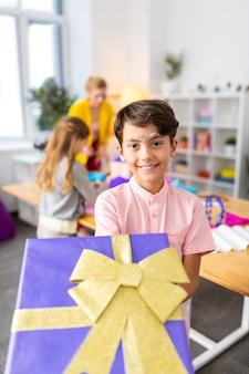 Fröhlicher schuljunge. dunkeläugiger fröhlicher schuljunge, der große geschenkbox mit goldenem jungen zeigt