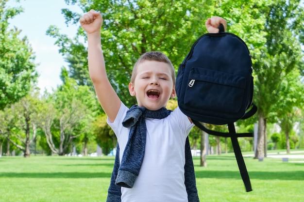 Fröhlicher schuljunge mit einem rucksack in den händen auf der straße auf dem weg zur schule. zurück zur schule.