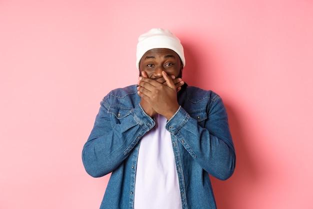 Fröhlicher schwarzer hipster-mann, der lachen hält, den mund bedeckt und über lustigen witz kichert, in die kamera starrt und kichert und auf rosafarbenem hintergrund steht.