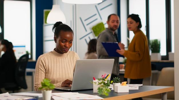 Fröhlicher schwarzer manager, der aufgaben auf dem laptop liest und am schreibtisch im geschäftigen start-up-büro sitzt, während das vielfältige team statistikdaten im hintergrund analysiert. multiethnische gruppe spricht über projekt