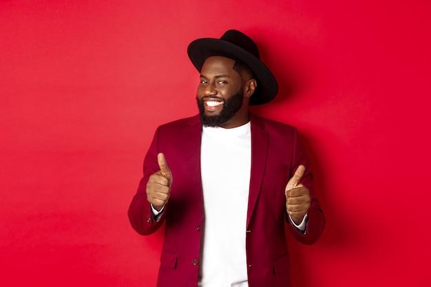 Fröhlicher schwarzer mann, der spaß auf der party hat, daumen hoch zeigt, lächelt und etwas mag, vor rotem hintergrund steht