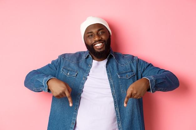Fröhlicher schwarzer mann mit bart, der hipster-kleidung trägt, mit den fingern nach unten zeigt und lächelt und promo-angebot-kopienraum, rosa hintergrund zeigt.