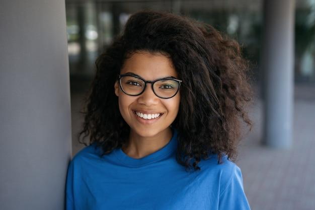 Fröhlicher selbstbewusster student, der eine stilvolle brille trägt und auf dem universitätscampus in die kamera schaut