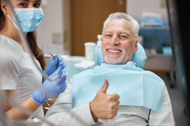 Fröhlicher senior, der beim zahnarzttermin mit seinem zahnarzt lächelt und daumen hoch zeigt und in die kamera schaut