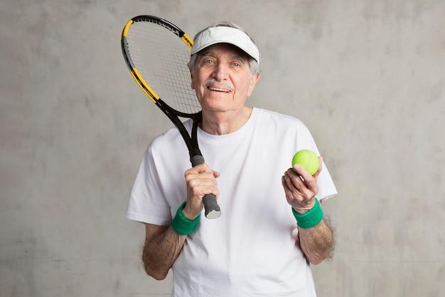 Fröhlicher senior tennisspieler mit schirmmütze
