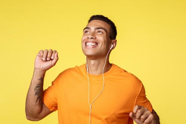 Fröhlicher sorgloser mann genießt perfekten sonnigen tag während des tagesspaziergangs, hebt eine hand faustpumpe, tanzt freudig, lächelt, genießt perfekten klang in kopfhörern, hört musikkopfhörer,