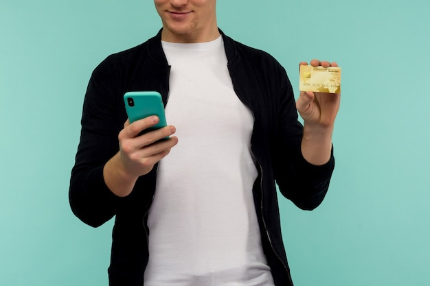 Fröhlicher sport rothaariger kerl führt online-zahlung durch und schaut auf den smartphone-bildschirm auf einem blauen hintergrund. - bild