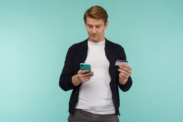 Fröhlicher sport rothaariger typ führt online-zahlungen durch und schaut auf das smartphone