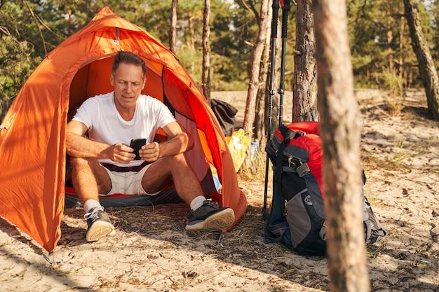 Fröhlicher sportlicher mann entspannt sich im zelt und nachrichten auf dem smartphone nach nordic walking im wald