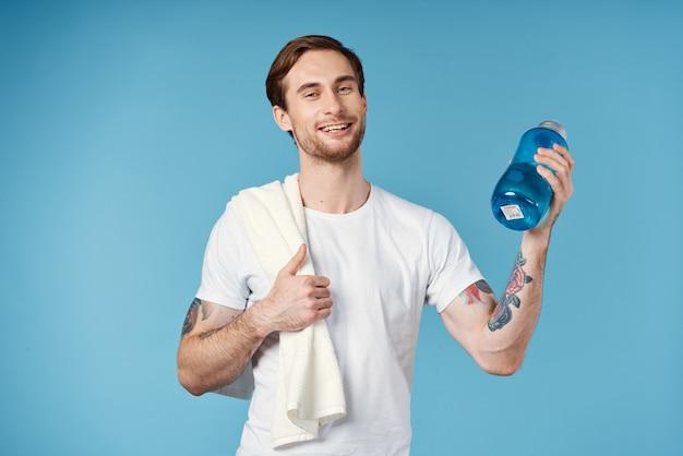 Fröhlicher sportlicher mann im weißen t-shirt wasserflasche energie blauen hintergrund