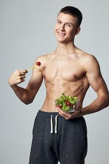 Fröhlicher sportlicher mann mit muskulösem nacktem körper, der gemüsesalat isst