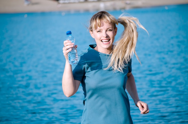 Fröhlicher sprung der jungen frau auf dem strand, der flasche süßwasser hält