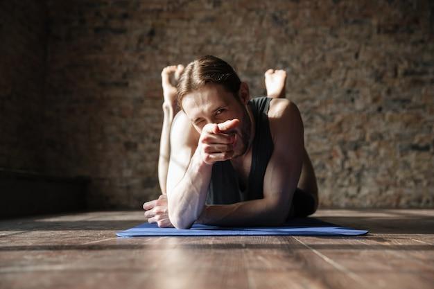 Fröhlicher starker sportler im fitnessstudio liegt auf dem boden und zeigt