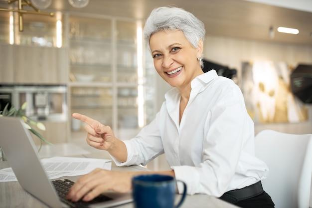 Fröhlicher stilvoller reifer weiblicher manager, der im büro arbeitet, am schreibtisch mit generischem tragbarem computer sitzt, breit lächelt, zeigefinger zeigt und ihren job genießt