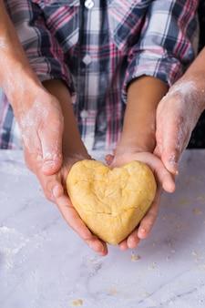 Fröhlicher süßer junge, der in den händen ein herzförmiges stück hausgemachten teig hält. familienzeit in der gemütlichen küche. herbstaktivität zu hause. hilfe und hausaufgabentraining für kinder