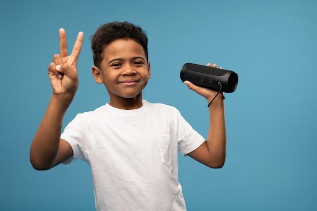 Fröhlicher süßer kleiner junge von afrikanischer athnizität, der friedensgeste zeigt, während spaß hat und musik in der drahtlosen intelligenten säule hört