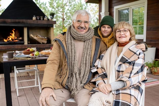 Fröhlicher süßer schuljunge und seine liebevollen großeltern in warmer freizeitkleidung, die dich mit einem lächeln gegen haus und tisch ansehen