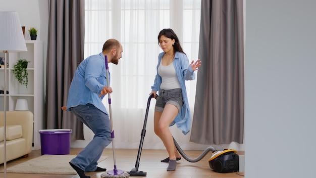 Fröhlicher tanzender mann und frau mit staubsauger und mopp beim reinigen des hauses