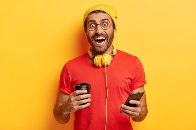 Fröhlicher tausendjähriger kerl steht mit kaffeetasse und smartphone