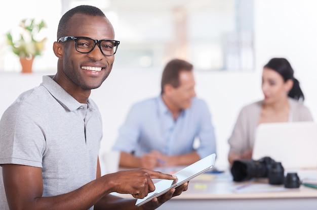 Fröhlicher teamleiter. hübscher junger afrikaner, der an digitalem tablet arbeitet und lächelt, während zwei leute am hintergrund arbeiten