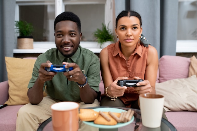 Fröhlicher teenager afrikanischer abstammung und gemischtrassiges mädchen, das auf der couch gegen das fenster im wohnzimmer sitzt und videospiele spielt