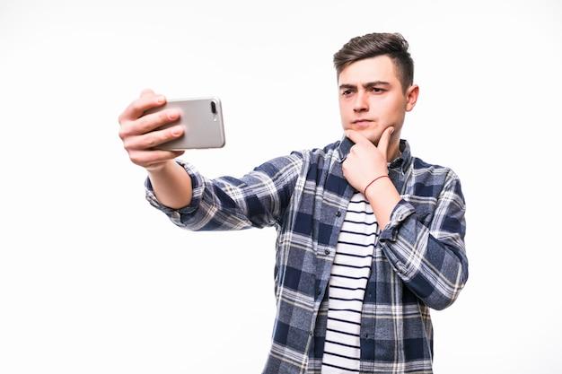 Fröhlicher teenager, der lustige selfies mit seinem handy nimmt